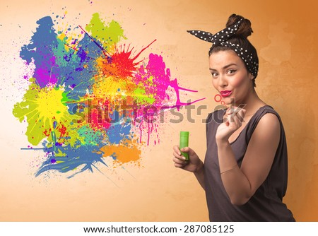 Cute girl blowing bubble spalsh graffiti into wall - stock photo