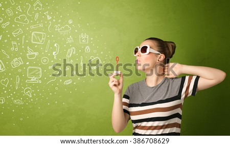 Cute girl blowing hand drawn media icons and symbols on green background - stock photo