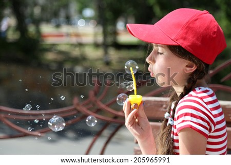 Cute girl blowing soap bubbles - stock photo