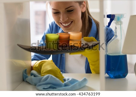 Cute girl cleans dust from shelves close up - stock photo