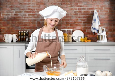 Cute girl cooking in kitchen at home