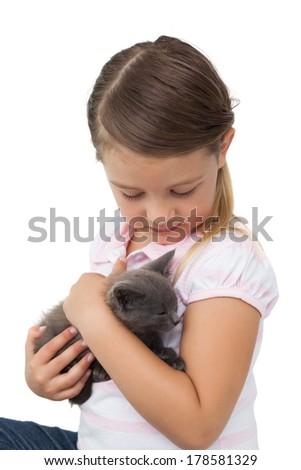 Cute girl cuddling grey kitten on white background - stock photo