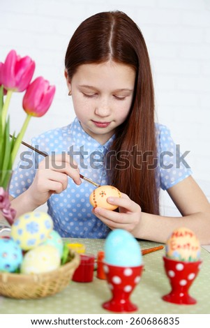 Cute girl decorates Easter eggs, on light background - stock photo