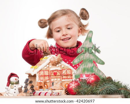 Cute girl decorating oneself made christmas cookies house - stock photo