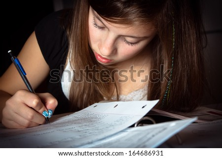 Cute girl doing school work in dramatic lighting