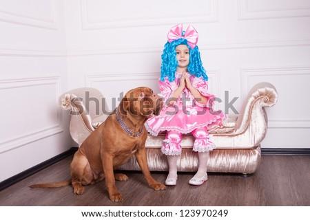 Cute girl dressed like Malvina with dog posing on sofa - stock photo