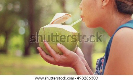 Cute Girl drinking coconut water .