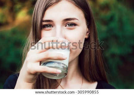 Cute girl drinks milk. portrait - stock photo