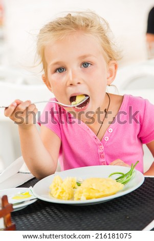 Cute girl eating lunch in outdoor cafe - stock photo