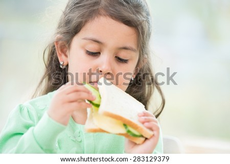 Cute girl eating sandwich at home