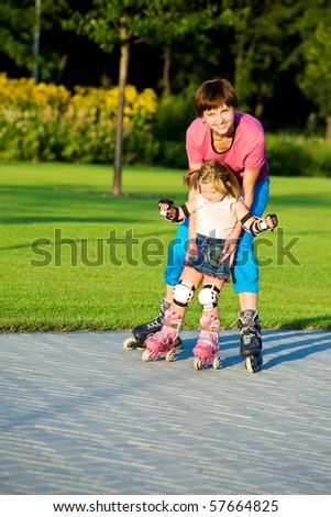 Cute girl first time in roller skates - stock photo