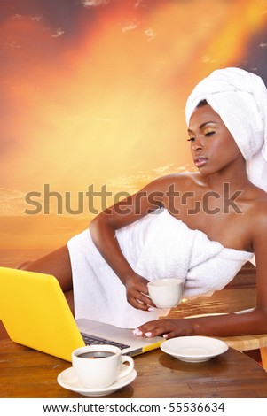 Cute girl gets her email while having her morning coffee - stock photo