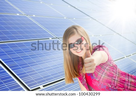 cute girl gives thumbs up for photovoltaic cells - stock photo