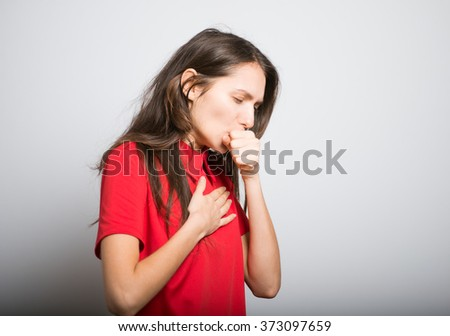 cute girl got sick and coughing, in a red dress, studio, isolated - stock photo