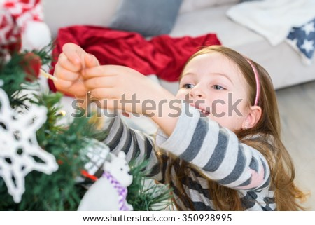Cute Girl Hanging Ornament on Christmas Tree