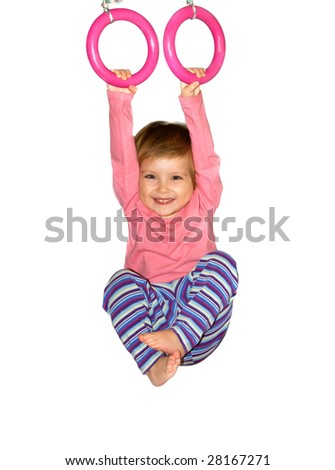 Cute girl hangs from rings on white background
