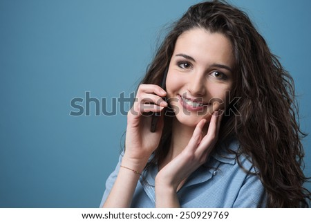 Cute girl having a phone call with her smart phone and touching her cheek