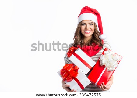 Cute girl holding a Christmas and New Year gifts. Christmas girl in santa hat with boxes isolated on white background. - stock photo