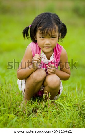 cute girl holding a grasshopper in her hand - stock photo