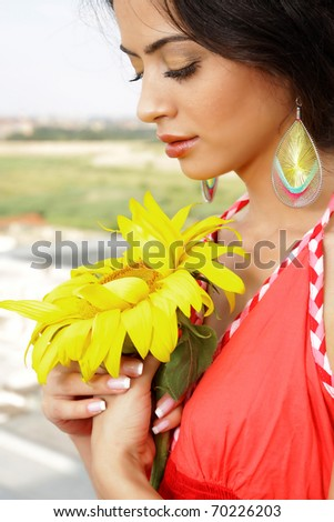 Cute girl holding a sunflower, eyes closed, make-up picture