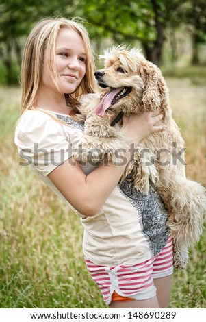 Cute girl holding funny looking dog - stock photo