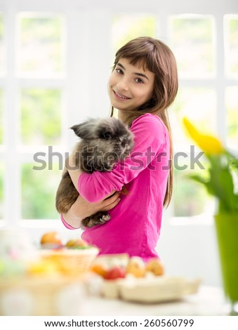Cute girl holding her adorable rabbit, concept Easter - stock photo