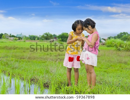 cute girl holding something (here a grasshopper) in her hand and showing it to her friend - stock photo