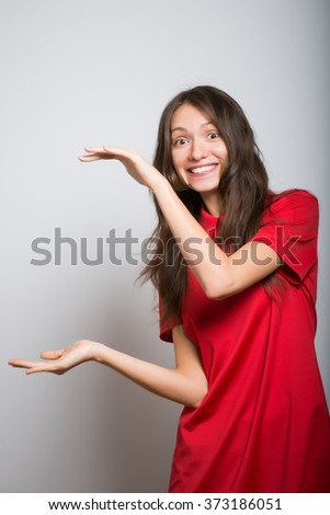cute girl holding something invisible hands in a red dress, studio, isolated - stock photo