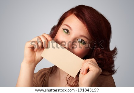Cute girl holding white card at front of her lips with copy space on gradient background - stock photo