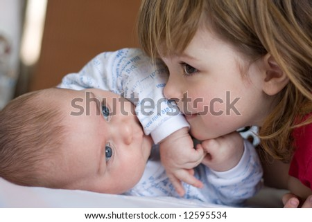 cute girl hugging her little brother, close up - stock photo