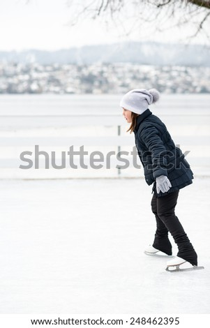 Cute girl ice skating on the ice rink with a beautiful view - stock photo