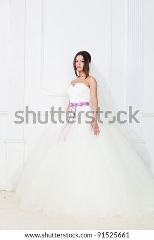 Cute girl in a gorgeous wedding dress with a ribbon