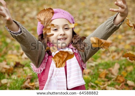 Cute girl in autumn park. Portrait shot.