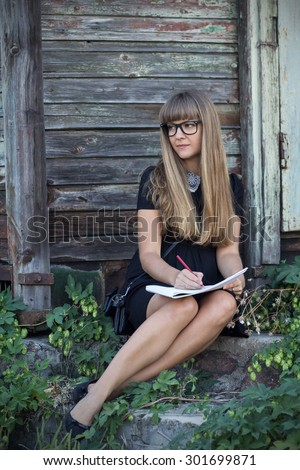 Cute girl in black glasses in the album draws on the steps of the old house - stock photo