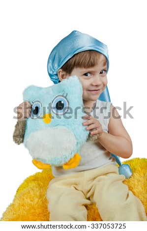 Cute girl in blue sleeping hat sitting with toy owl isolated on white - stock photo