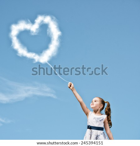 Cute girl in dress with heart shaped balloon on rope - stock photo