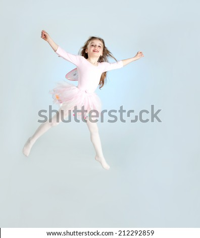 Cute girl in fairy costume jumping in the studio