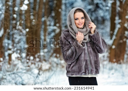 Cute girl in grey fur coat winter forest background - stock photo
