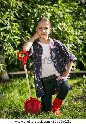 Cute girl in gumboots posing with toy spade at garden