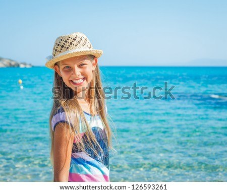 Cute girl in hat on the beach - stock photo
