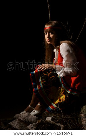 cute girl in national costume posing in darkness
