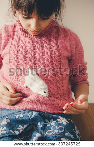 Cute girl in pink playing with her white hamster - stock photo