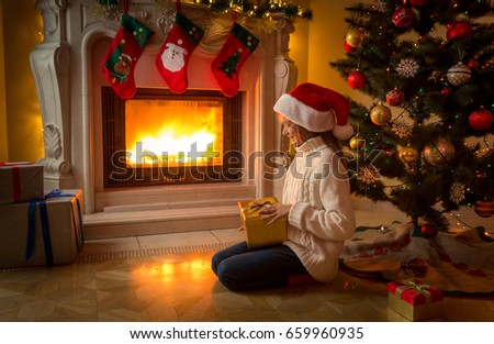 Cute girl in Santa hat sitting with Christmas gift at fireplace