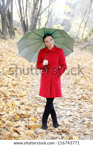 cute girl in the autumn forest with umbrella by day - stock photo