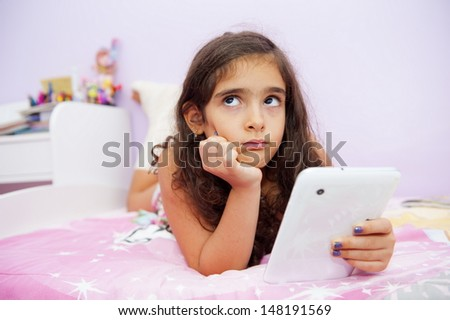 Cute girl in the bed with a tablet  - stock photo