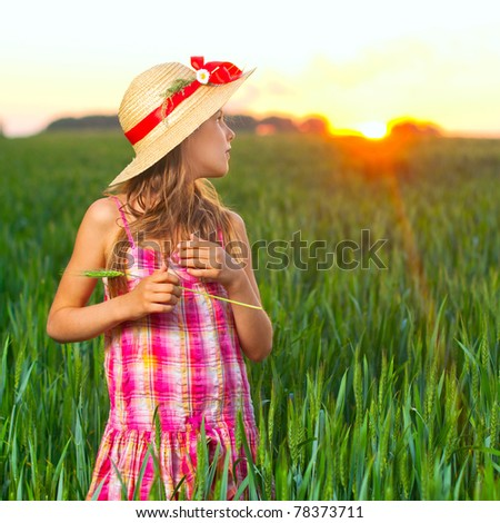 Cute girl in the straw hat with red ribbon on green wheat. - stock photo