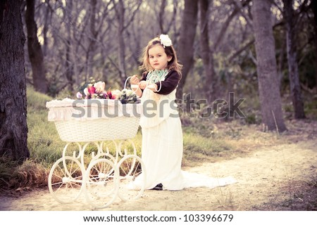 Cute girl in vintage clothes with flowers in pram - stock photo