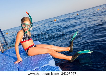 Cute girl in water mask and swim fins sitting on pontoon ready to jump into water - stock photo