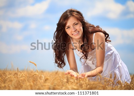 Cute girl in wheat field enjoying in summer