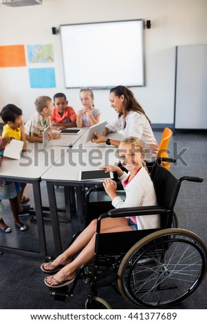 Cute girl in wheelchair posing for the camera in classroom - stock photo